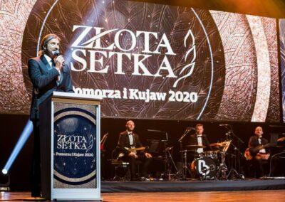zdjęcie zuroczystej gali, przedstawiające scenę, orkiestrę orazprowadzącego